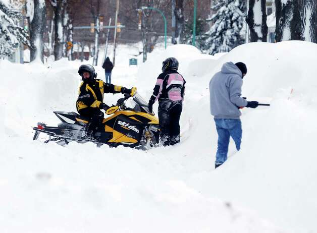 A snowmobile is forced to turn around on a snow-clogged street in the south Buffalo area on Thursday, Nov. 20, 2014, in Buffalo, N.Y.  A new blast of lake-effect snow pounded Buffalo for a third day piling more misery on a city already buried by an epic, deadly snowfall that could leave some areas with nearly 8 feet of snow on the ground when it's all done. (AP Photo/Mike Groll) ORG XMIT: NYMG118 Photo: Mike Groll, AP / AP
