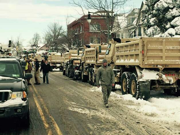 In this photo released by the New York National Guard, New York Army National Guard dump trucks line up on West Seneca Street, Thursday, Nov. 20, 2014, in Buffalo, N.Y., to help clear snow from the city. A new blast of lake-effect snow pounded Buffalo for a third day piling more misery on a city already buried by an epic, deadly snowfall that could leave some areas with nearly 8 feet of snow on the ground when it's all done. (AP Photo/New York National Guard, Maj. Mark Frank) ORG XMIT: NY1221 Photo: Maj. Mark Frank, AP / New York National Guard