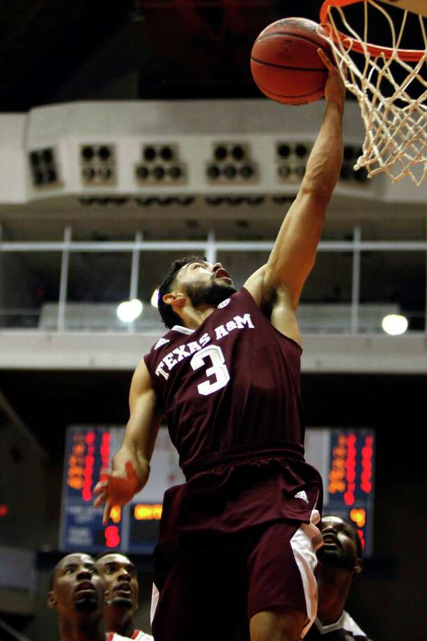 Texas A&M guard Alex Robinson goes up for a shot against Dayton players during an NCAA college basketball game against Texas A&M in San Juan, Puerto Rico, Thursday, Nov. 20, 2014. (AP Photo/Ricardo Arduengo) Photo: Ricardo Arduengo, Associated Press / AP