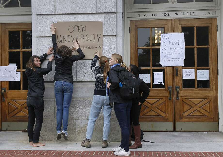 Students tape a sign to Wheeler Hall at UC Berkeley on Thursday, Nov. 20, 2014. The students are protesting a 5% tuition increase approved by a University of California Board of Regents committee Wednesday. The full board is expected to pass the increase Thursday. Photo: Paul Chinn, The Chronicle