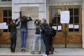 Students tape a sign to a Wheeler Hall wall at UC Berkeley on Nov. 20, 2014. The students are protesting a 5 percent tuition increase approved by a University of California Board of Regents. The full board pased the increase Thursday.