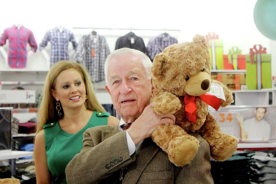 """Pearland Mayor Tom Reid checks out a """"Bears That Care"""" as Bria Lundy (PR Director Stage Stores Inc) looks on. Stage Stores, Inc. is made a $100,000 donation to Toys for Tots at the grand opening of the newly relocated Palais Royal Department Store in Pearland, to kick off the holiday season and the 2014 """"Bears That Care"""" program. Photo: Pin Lim, Freelance / Copyright Pin Lim"""
