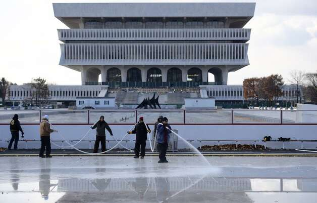 The holiday season has arrived as state Offiice of General Services workers put down water for the ice rink at the Empire Plaza in Albany. The rink opens Nov. 28, weather permitting. (Skip Dickstein/Times Union)