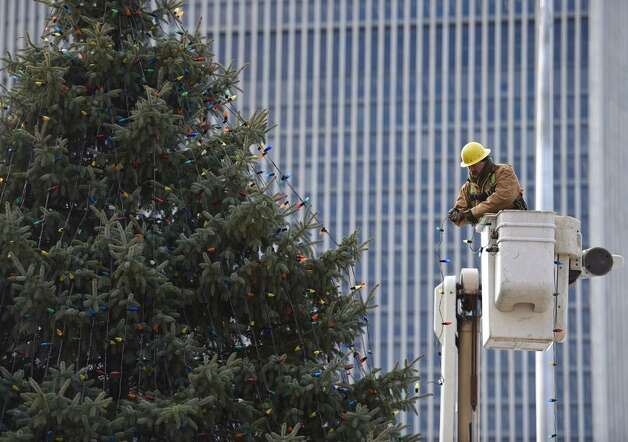 A state Office of General Services worker strings lights on the state holiday tree at the Empire State Plaza in Albany. The official tree lighting is scheduled for 5:15 Dec. 7. (Skip Dickstein/Times Union)