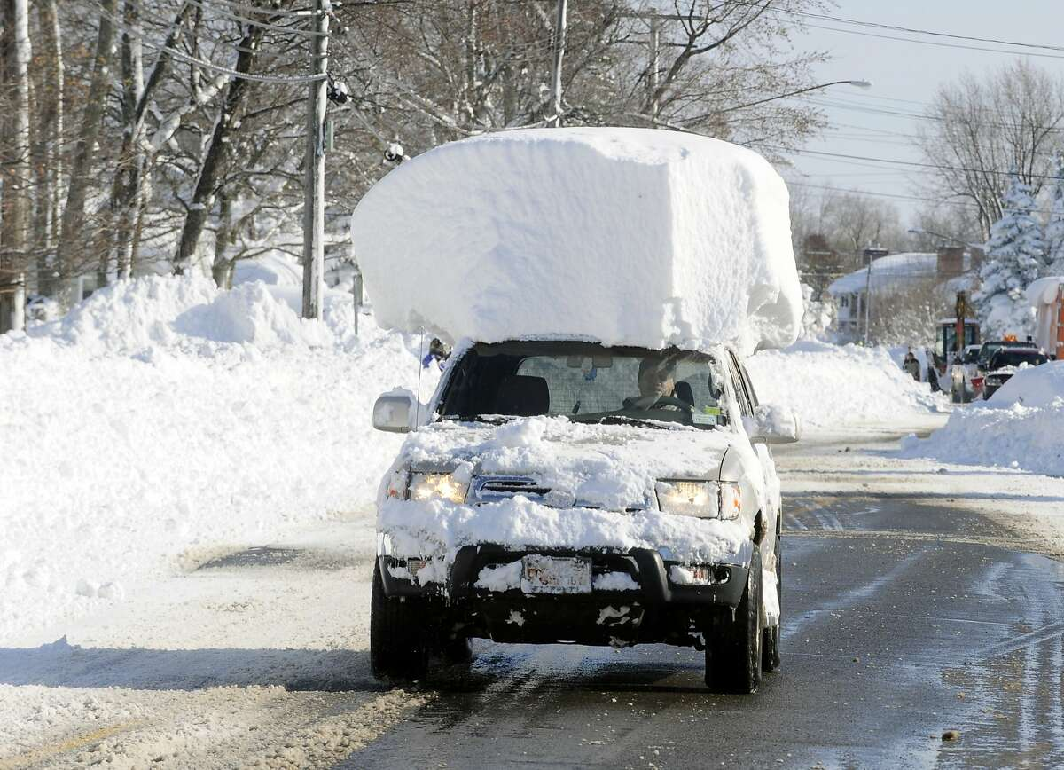 WHO NEEDS A SKI RACK? A vehicle with a small mountain of snow on its top drives along Route 20 after digging out after a massive snowfall in Lancaster, N.Y.