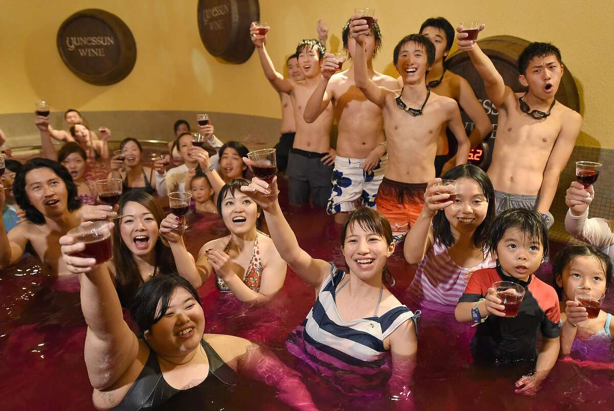 TURNING WATER INTO WINE: Bathers raise their glasses containing 2014 vintage Beaujolais Nouveau wine at a wine spa in Hakone, Japan, for the annual uncorking of the vintage on the third Thursday in November. No word if the purplish wine bath has medicinal qualities.