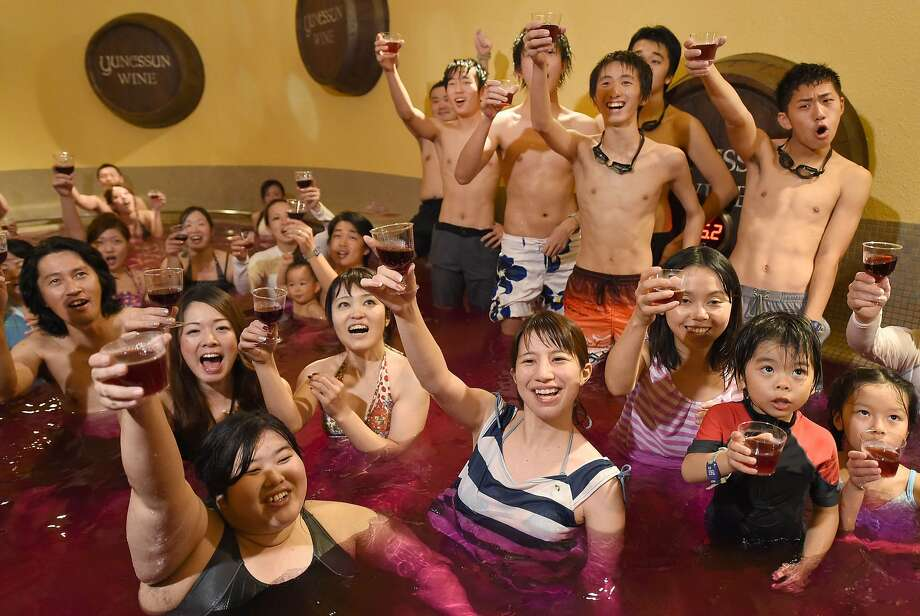 TURNING WATER INTO WINE:Bathers raise their glasses containing 2014 vintage Beaujolais Nouveau wine at a wine spa in Hakone, Japan, for the annual uncorking of the vintage on the third Thursday in November. No word if the purplish wine bath has medicinal qualities. Photo: Toru Yamanaka, AFP/Getty Images