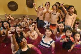 """Bathers raise their glasses, containing 2014 vintage Beaujolais Nouveau wine, at a """"wine spa"""" in Hakone town, Kanagawa prefecture, some 100-kilometres west of Tokyo on November 20, 2014, after an embargo on the wine was removed. A total of seven million bottles of Beaujolais Nouveau wine are expected to be imported into Japan this year."""