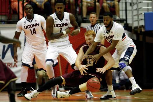 Charleston center David Wishom battles for a loose ball against UCONN guard Sam Cassell Jr., right, during an NCAA college basketball game in San Juan, Puerto Rico, Thursday, Nov. 20, 2014. Photo: Ricardo Arduengo, AP / Associated Press