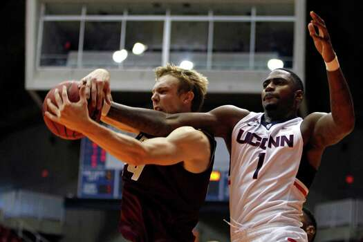 Charleston guard Canyon Barry, left, battles for a rebound against UCONN forward Phillip Nolan, during an NCAA college basketball game in San Juan, Puerto Rico, Thursday, Nov. 20, 2014. Photo: Ricardo Arduengo, AP / Associated Press