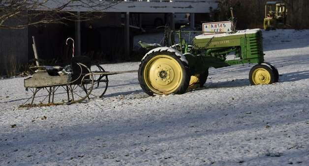 Snow covers this tractor, sleigh and grass in Berne in rural Albany County on Friday, Nov. 14, 2014. (Skip Dickstein / Times Union) ORG XMIT: MER2014111413145914