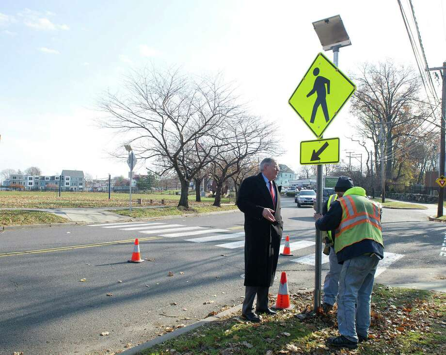 Stamford Mayor David Martin watches as city workers install a solar-powered crosswalk sign at the intersection of Stillwater Ave. and Progress Drive in Stamford, Conn., on Thursday, November 20, 2014. Photo: Lindsay Perry / Stamford Advocate