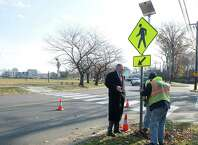 Stamford Mayor David Martin watches as city workers install a solar-powered crosswalk sign at the intersection of Stillwater Ave. and Progress Drive in Stamford, Conn., on Thursday, November 20, 2014.