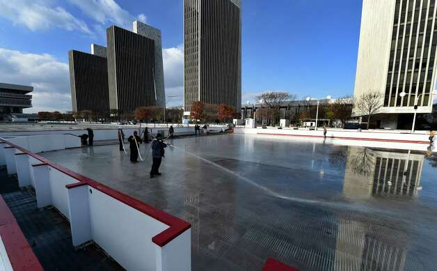 Workers from the NYS OGS-Grounds spray water on the ice rink Thursday morning Nov. 20, 2014 on the Empire State Plaza in Albany, N.Y.  The popular seasonal ice rink will open to the public on Nov. 28th.        (Skip Dickstein/Times Union) Photo: SKIP DICKSTEIN