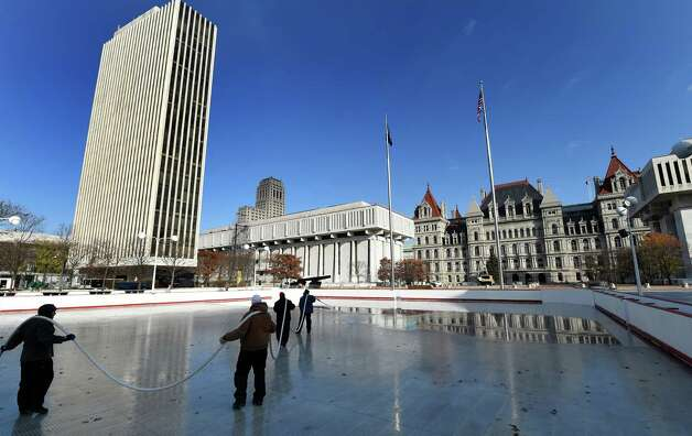 Workers from the NYS OGS-Grounds spray water on the ice rink surface Thursday morning, Nov. 20, 2014, at the Empire State Plaza in Albany, N.Y. The popular seasonal ice rink scheduled to open Friday November 28, weather permitting. (Skip Dickstein/Times Union) Photo: SKIP DICKSTEIN