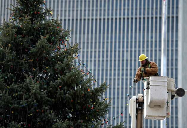 A worker from NYS OGS-Grounds string some of the 2400 lights on the State Holiday Tree Thursday morning, Nov. 20, 2014, on the Empire State Plaza in Albany, N.Y. The lights will turned on Dec. 7th at 5:15 p.m. during a special event. (Skip Dickstein/Times Union) Photo: SKIP DICKSTEIN