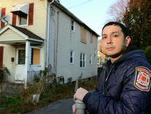 Bridgeport firefighter Bobby Hernandez poses outside of the home on Bennett Street where he and fellow firefighter Richard Messer rescued a 93 year old woman from the secong floor after a fire last night in Bridgeport, Conn., on Thursday Nov. 20, 2014.