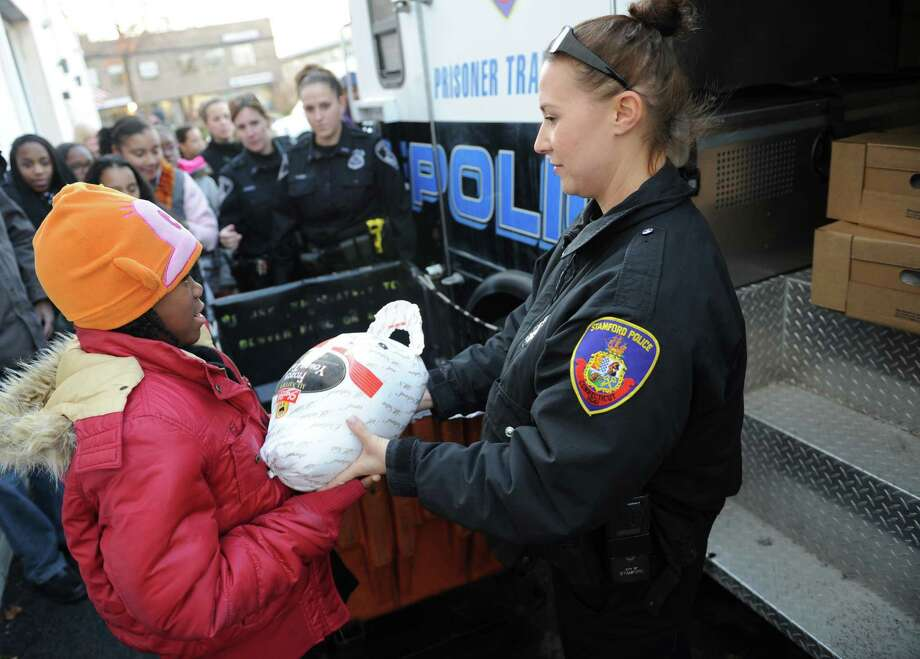 Stamford Police Officer Nicole Petrenko hands a frozen turkey from a prisoner transport vehicle to Miracle McBride, 11, of Stamford, to donate at the Food Bank of Lower Fairfield County in Stamford, Conn. Thursday, Nov. 20, 2014.  The Stamford Police Association donated 55 turkeys to the food bank with the help of girls from SPA's Girls Leadership Program.  The leadership program works with the Domus Foundation to match the middle-school girls with female police officers for mentoring and educational opportunities.  The food bank gave out 15,000 turkeys last Thanksgiving and recently advised that is it 800 short of its goal this year. Photo: Tyler Sizemore / Greenwich Time