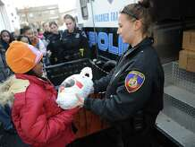 Stamford Police Officer Nicole Petrenko hands a frozen turkey from a prisoner transport vehicle to Miracle McBride, 11, of Stamford, to donate at the Food Bank of Lower Fairfield County in Stamford, Conn. Thursday, Nov. 20, 2014.  The Stamford Police Association donated 55 turkeys to the food bank with the help of girls from SPA's Girls Leadership Program.  The leadership program works with the Domus Foundation to match the middle-school girls with female police officers for mentoring and educational opportunities.  The food bank gave out 15,000 turkeys last Thanksgiving and recently advised that is it 800 short of its goal this year.