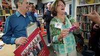 David Finfrock holds his 1965 class photo as he and Cindy Campbell share a moment in the library during a tour of Parker Elementary School in Houston.