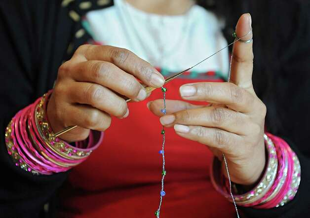 Volunteer Budhi Darjee of Rensselaer crochets a bead necklace for the Black Friday Fair Trade Market at the Delmar Reformed Church on Tuesday, Nov. 18, 2014 in Delmar,  N.Y. Budhi is a Bhutanese refugee. The Black Friday Fair Trade Market will be going on next weekend. (Lori Van Buren / Times Union) Photo: Lori Van Buren / 00029523A
