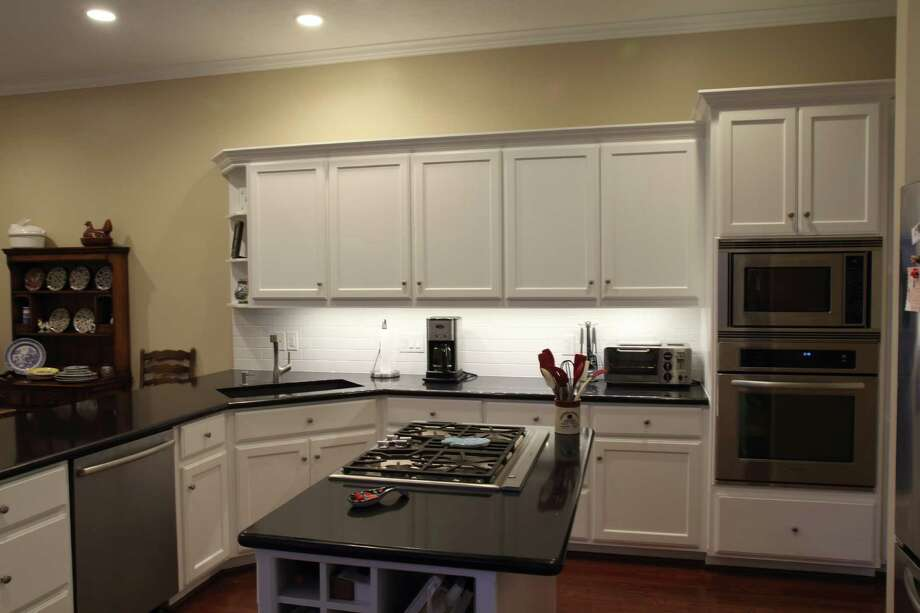 This remodeled kitchen by Abbott Contracting includes a backsplash and light fixtures under the top cabinets.