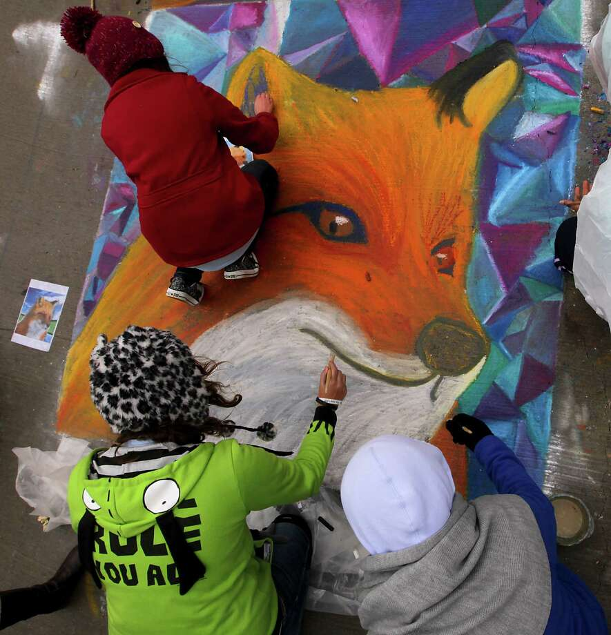 Artist work on an art piece during the Via Colori The Street Painting Festival in downtown Saturday, Nov. 23, 2013, in Houston.  ( James Nielsen / Houston Chronicle ) Photo: James Nielsen, Staff / © 2013  Houston Chronicle