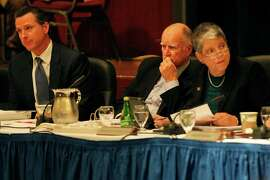 """Gov. Jerry Brown (center) and UC President Janet Napolitano listen as students and members of the public chant, """"Hey ho, hey ho, tuition hikes have got to go"""" during the public comment period of a closed UC regents meeting at UCSF Mission Bay on Nov. 20."""
