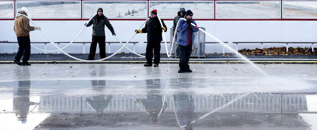 Workers from the NYS OGS-Grounds spray water on the ice rink surface Thursday morning, Nov. 20, 2014, at the Empire State Plaza in Albany, N.Y. The popular seasonal ice rink scheduled to open Friday November 28, weather permitting. (Skip Dickstein/Times Union) ORG XMIT: MER2014112017261525 Photo: SKIP DICKSTEIN, ALBANY TIMES UNION