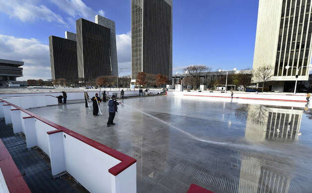 Workers from the NYS OGS-Grounds spray water on the ice rink surface Thursday morning, Nov. 20, 2014, at the Empire State Plaza in Albany, N.Y. The popular seasonal ice rink scheduled to open Friday November 28, weather permitting. (Skip Dickstein/Times Union) ORG XMIT: MER2014112017300327 Photo: SKIP DICKSTEIN, ALBANY TIMES UNION