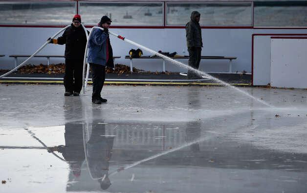 Workers from the NYS OGS-Grounds spray water on the ice rink surface Thursday morning, Nov. 20, 2014, at the Empire State Plaza in Albany, N.Y. The popular seasonal ice rink scheduled to open Friday November 28, weather permitting. (Skip Dickstein/Times Union) Photo: SKIP DICKSTEIN, ALBANY TIMES UNION