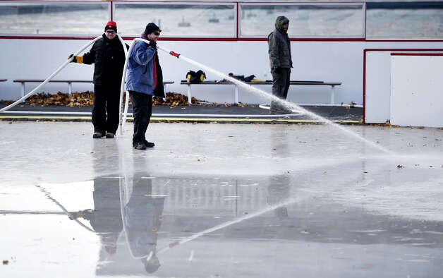 Workers from the NYS OGS-Grounds spray water on the ice rink surface Thursday morning, Nov. 20, 2014, at the Empire State Plaza in Albany, N.Y. The popular seasonal ice rink scheduled to open Friday November 28, weather permitting. (Skip Dickstein/Times Union) ORG XMIT: MER2014112017261826 Photo: SKIP DICKSTEIN, ALBANY TIMES UNION