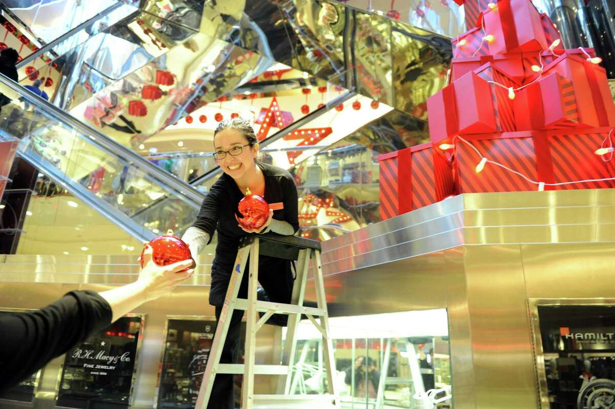 Maribel Tieber works on a holiday display Thursday, Nov. 20, 2014 at Macy's in the Danbury Fair mall.