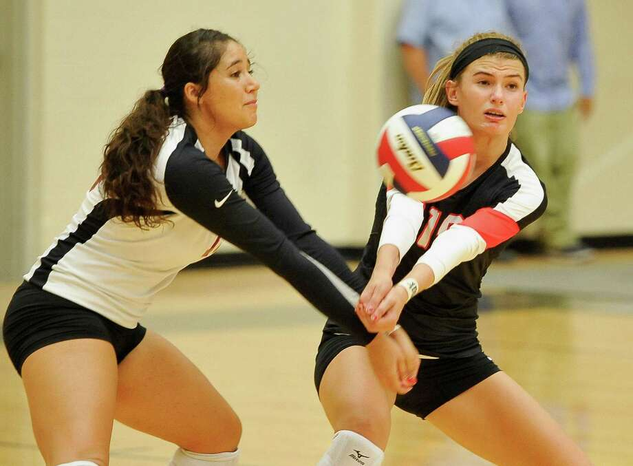Churchill's Ashley Dominguez, left, and Cate Buckingham, return the ball during a high school volleyball match against O'Connor, Monday, Aug. 11, 2014, at NEISD Littleton Gymnasium in San Antonio. Churchill won 3-1. Photo: Darren Abate / Darren Abate / Darren Abate/Express-News