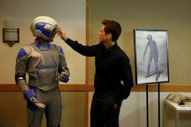 Actor Rod Lowe takes a closer look at the helmet on Adi Rao, who is wearing the Genworth R70, a suit that simulates the effects of aging.