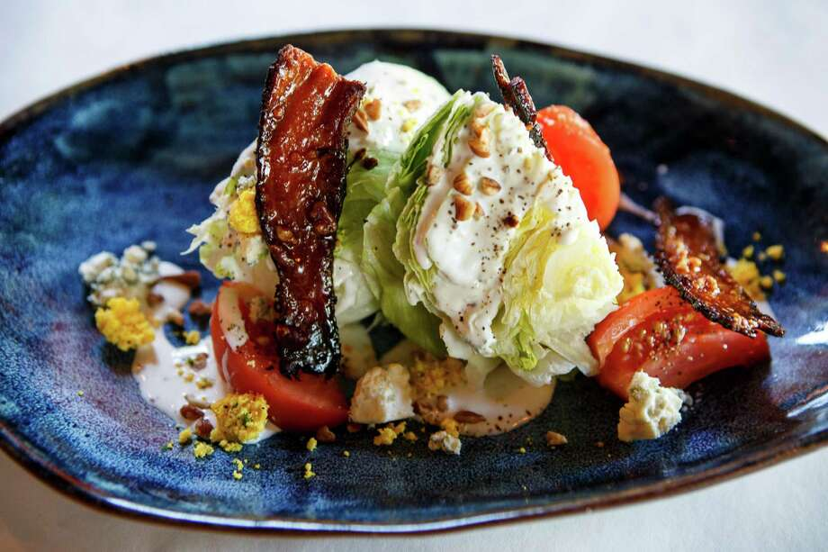 Iceberg lettuce, tomato, praline bacon, pecans, blue cheese, and buttermilk dressing combine in the wedge salad. Photo: Spencer Selvidge / Spencer Selvidge / For The San Antonio Express-News / © 2014 San Antonio Express-News