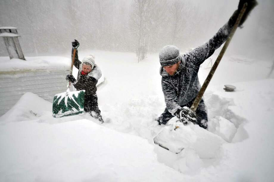 Tami Normile and Richard Brooks remove snow from the rooftop of a home   in   Buffalo, N.Y. The region typically gets 8 feet of snow yearly. Nearly that much has fallen in three days. Photo: John Normile / John Normile / Getty Images / 2014 Getty Images