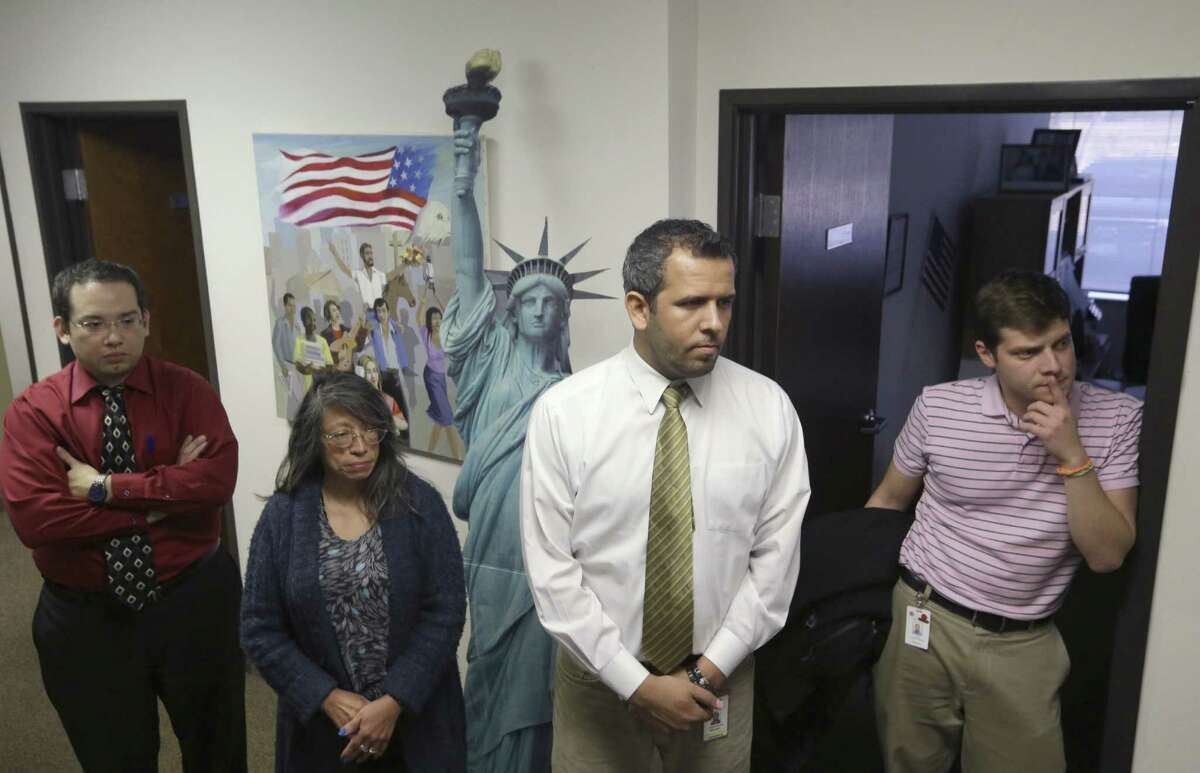 Members of the staff at the immigration and legal services office of Catholic Charities, from left, David Rosales, Rosario Mezo, Hassan Alzuhwira, and Luis Miguel Arango, listen during an impromptu meeting about the pending immigration action announcement by President Obama in Dallas, Thursday, Nov. 20, 2014. Attorneys and advocacy groups are organizing and preparing for efforts to serve immigrants in Texas who will look to qualify under a White House plan to protect them from deportation.