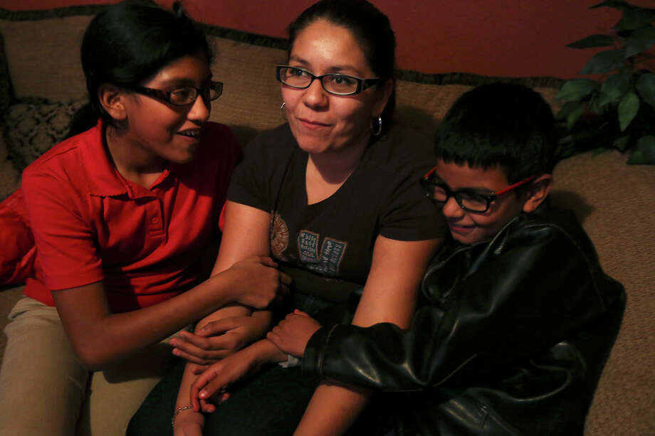 After a day of cleaning houses, Epifania Gonzalez, 32, arrives home to her children in the city's southwest side, Thursday, Nov. 20, 2014. Gonzalez is in the country illegally but her four children are U.S. citizens. She hopes that President Obama's executive order will allow her to come out of the shadows. The single mother lost her husband in a car accident after he was deported back to Mexico in 2011. With her is her daughter Maria Buendia, 13, left, and son, Baudel Buendia, 9. Her son has fought leukemia twice and is in remission. Photo: JERRY LARA, San Antonio Express-News / © 2014 San Antonio Express-News
