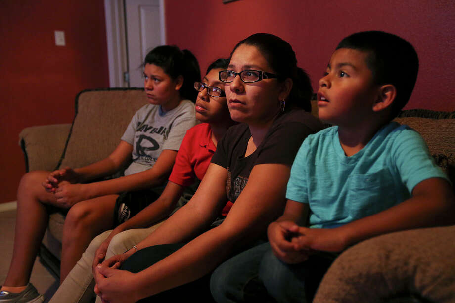 After a day of cleaning houses, Epifania Gonzalez, 32, watches television with her children at their home in the city's southwest side, Thursday, Nov. 20, 2014. Gonzalez is in the country illegally but her four children are U.S. citizens. She hopes that President Obama's executive order will allow her to come out of the shadows. The single mother lost her husband in a car accident after he was deported back to Mexico in 2011. With her are her children from left, Maria Buendia, 13, Alejandra Buendia, 11, and Christopher Buendia, 4. Photo: JERRY LARA, San Antonio Express-News / © 2014 San Antonio Express-News