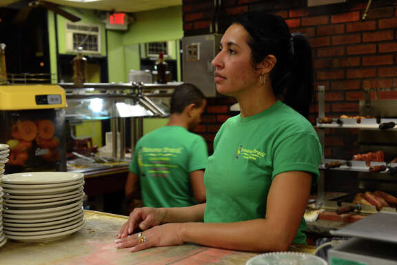 Between customers, Banana Brazil employee Marlene Quintao listens to President Obama on television at Banana Brazil restaurant in Danbury, Conn. on Thursday Nov. 20, 2014. President Obama spoke to the nation about his plan to extend deportation protection and legal job status to some 5 million undocumented immigrants. Members of CT Students for a DREAM, which advocates for the rights of undocumented workers across the state, gathered at the restaurant to watch the president speak.