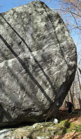 Photo by Herb Terns. A hiker passes under a glacial erratic on an unnamed peak in the Dix Mountain Wilderness. Photo: Picasa