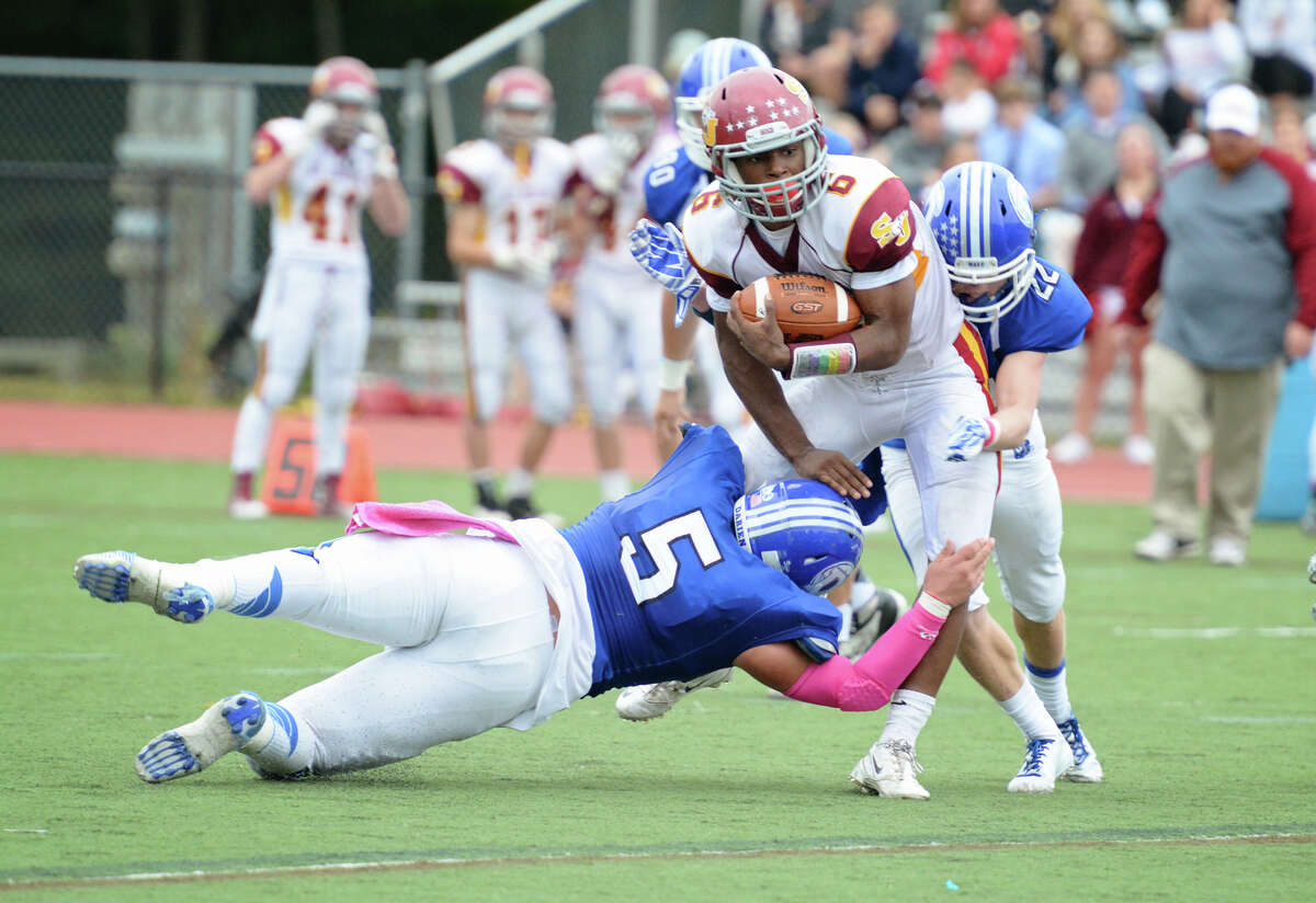 Darien's George Reed (5) and Hudson Hamill (22) defend against St. Joseph ball carrier Mufasha Abdul Basir (6) during the football game against St. Joseph's High School at Darien on Thursday, Oct. 2, 2014.