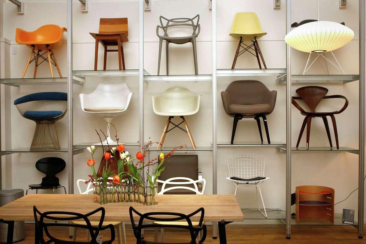 A chair display features designers such as Herman Miller, Knoll, Jacobsen, De La Espada, Kartell and Cherner.