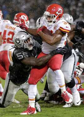 Oakland Raiders outside linebacker Sio Moore (55) tackles Kansas City Chiefs running back Knile Davis (34) during the second quarter of an NFL football game in Oakland, Calif., Thursday, Nov. 20, 2014. (AP Photo/Marcio Jose Sanchez)