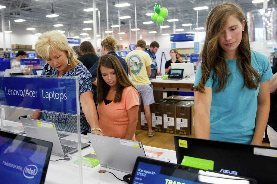 FILE - In this Aug. 1, 2014 file photo, Caroline Head, right, clicks through websites on a laptop during a sales tax holiday sale at Best Buy on in Augusta, Ga. Best Buy on Thursday, Nov. 20, 2014 said its revenue edged up in the third quarter, a positive sign for the electronics retailer as the holiday season kicks off. (AP Photo/The Augusta Chronicle, Sara Caldwell, File) ORG XMIT: GAAUG401 Photo: Sara Caldwell / The Augusta Chronicle