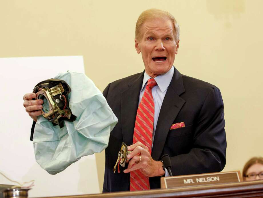 Senate Commerce Committee member Sen. Bill Nelson, D-Fla. displays the parts and function of a defective airbag made by Takata of Japan that has been linked to multiple deaths and injuries in cars driven in the U.S., Thursday, Nov. 20, 2014, during the committee's hearing on Capitol Hill in Washington. Hiroshi Shimizu, Takata Corp.'s Senior Vice President of Quality, told the committee that a national recall of driver's side air bag inflators is not necessary, and should be limited to high-humidity areas. (AP Photo/J. Scott Applewhite) ORG XMIT: DCSA103 Photo: J. Scott Applewhite / AP