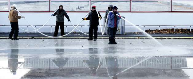 Workers from the NYS OGS-Grounds spray water on the ice rink surface Thursday morning, Nov. 20, 2014, at the Empire State Plaza in Albany, N.Y. The popular seasonal ice rink scheduled to open Friday November 28, weather permitting. (Skip Dickstein/Times Union) ORG XMIT: MER2014112017261525 Photo: SKIP DICKSTEIN