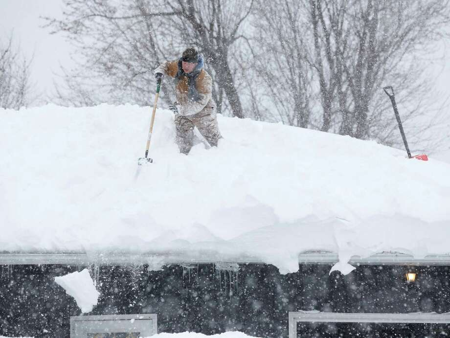 Tom Mudd clears snow from the roof of his house on Thursday, Nov. 20, 2014, in Cheektowaga, N.Y. A new blast of lake-effect snow pounded Buffalo for a third day piling more misery on a city already buried by an epic, deadly snowfall that could leave some areas with nearly 8 feet of snow on the ground when it's all done. (AP Photo/Mike Groll) ORG XMIT: NYMG27 Photo: Mike Groll / AP