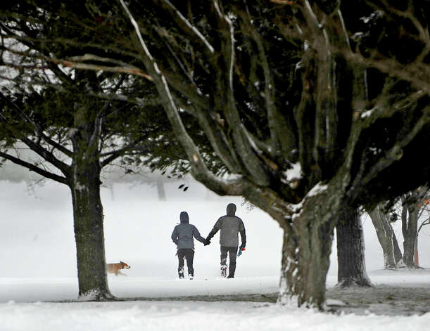 A couple take their dog for a walk on the trails through the Watertown Golf Club in Watertown, N.Y. on Thursday, Nov. 20, 2014.   A new blast of lake-effect snow pounded Buffalo for a third day piling more misery on a city already buried by an epic, deadly snowfall that could leave some areas with nearly 8 feet of snow on the ground when it's all done.  (AP Photo/The Watertown Daily Times, Amanda Morrison)  ORG XMIT: NYWAT202 Photo: Amanda Morrison / © Watertown Daily Times 2013